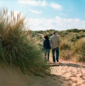 Couple walking through sand dunes on beach at Aberdeen