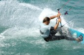 Kitesurfer carving through wave in strong winds