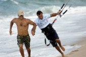 Kitesurfer is pulled pulled along beach by friend