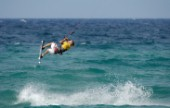 Kitesurfer gets air off a wave in strong breeze