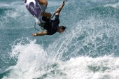 Kitesurfer get big air off wave in strong winds