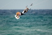 Kitesurfer tangled in kite lines in mid air