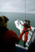 Coastguard Rescue Worker preparing to be winched down from Helicopter