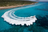 A power boat performs a 180¼ turn by the shore creating a doily effect wash