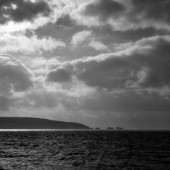 Strong SW wind bringing changeable conditions. Needles rocks and Isle of Wight silhouetted with band of sun on sea. Lots of cumulus clouds. needles isle wight black white solent uk clouds sky