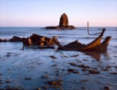 Early sun on a barnacle encrusted iron wreck at Saltwick,Yorkshire. Sun glints off seaweed, sky reflected in wet slate. Sun also illuminates rock monolith. Pink horizon, with a freighter on it.wreck abandoned rocks seashore disaster beach sunrise atmospheric