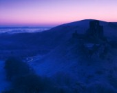 A harsh frost before dawn at Corfe in Dorset with mist on the plain near Poole Harbour. The Castle ruins are in near silhouette against East hill. This cool image colour was created by the intentional use of Tungsten film.
