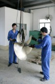 Yacht builders and skilled workers boatbuilding at the Cheoy Lee shipyard and boatbuilders in China. Manufacturing propellers.