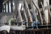 Yacht builders and skilled workers boatbuilding at the Cheoy Lee shipyard and boatbuilders in China. Welders welding.