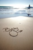 Baby boy congratulations sign writing message on a sandy beach in Tarifa, Spain, near Gibraltar.