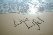 One Life - Live it sign writing message on a sandy beach in Tarifa, Spain, near Gibraltar.