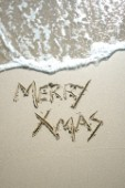Merry Christmas Xmas sign writing message on a sandy beach in Tarifa, Spain, near Gibraltar.