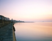 A calm and atmospheric sunrise at the Promenade in Penzance with the Jubilee Pool and St Michaels Mount in the distance. Limited Edition prints available.