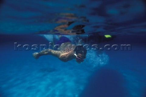 Man snorkelling in clear blue shallow water