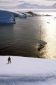 Man standing on icey ridge above anchored yacht