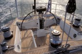 Wheel of Swan 68 under autopilot with teak deck and mainsheet blocks