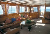 Model Jilly Johnson relaxing in the interior saloon of superyacht Antilles