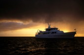 Superyacht Antilles in the sunset before a storm