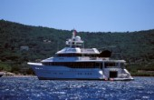 Superyacht at anchor with a Jet Ranger helicopter on the aft deck