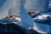 The crew of the giant 182ft schooner Adela, owned by American George Lindemann, demonstrates the commitment and technique reserved for only the most professional of crews. As the yacht changes course from a run downwind onto a reach, there is a need to reduce sail. The crewmember controlling the spinnaker halyard uses precise judgement in controlling the drop of the 1000 sq metre sail at the same rate as the crew is gathering it in onto the deck. The skill is making the giant sail hover across the water allowing wind to still pass under it. Just a few metres too much halyard released too quickly and the sail fills with water stopping the 350 ton yacht and potentially breaking expensive sails, equipment, spars and members of her crew. Maxi Yacht Rolex Cup 2001. Porto Cervo, Sardinia.