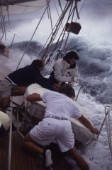 Three crew men working in teamwork secure a dinghy on deck in rough seas and waves