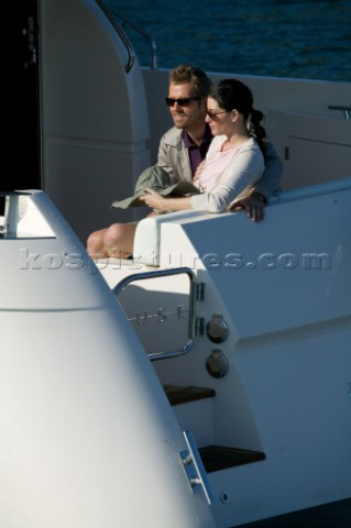 Couple sitting on aft of  a power boat
