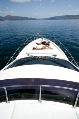 Two women sunbathing on powerboat