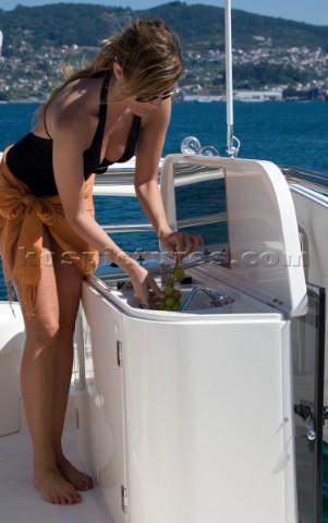 Woman washing grapes in a sink on a yacht