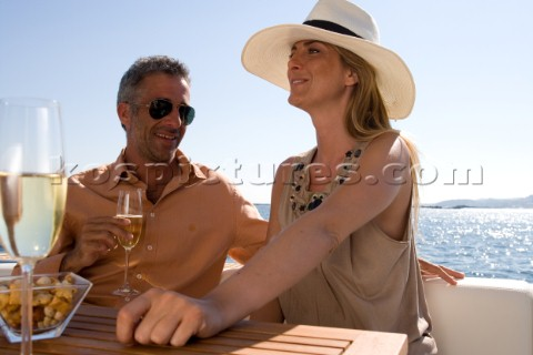 Couple sitting on a yacht drinking champagne