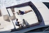 Man driving a powerboat and woman sunbathing.