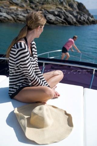 Woma sitting on powerboat looking at a man