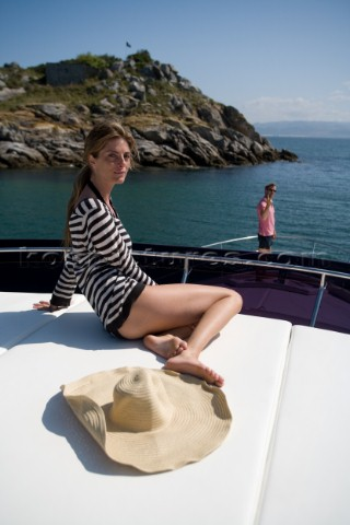Woam sitting on powerboat looking at camera