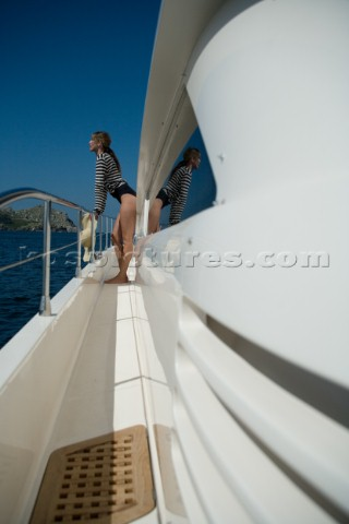 Woman in swimsuit standing on the side of a yacht