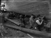 Caulking team work on a hull at Grove & Gutteridge yard in Cowes, Isle of Wight, in the 1930s
