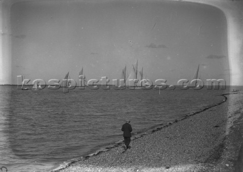 Man walking on the beach during a Big Class regatta off Cowes on the Solent