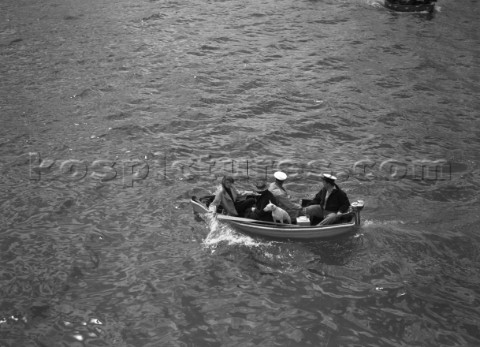 Spectators and a dog in a tender during the international mboat race in Torquay 1938