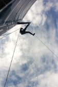 Low angle view of a man climbing a mast