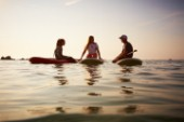 Two girls and a man sitting on paddleboards