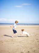 Boy playing with a dog on the beach