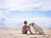 Woman sitting on beach with a dog