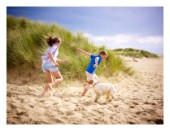 Children playing in the sand with a dog