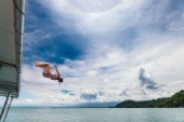A girl jumps from the roof of a boat into the ocean off the coast of Costa Rica.