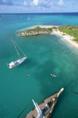 Masthead, aerial view of cruising sailboats at anchor off Green Island, Antigua, British West Indies, in the Caribbean Sea.