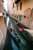 A gondola with tourists sails through a narrow canal in Venice, Italy.