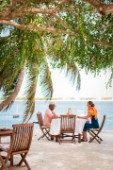 A man and woman sit under shade trees at a table on a patio overlooking the blue water of Lamu Channel.