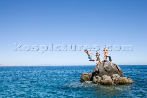 A mother and her three kids jump from an isolated rock into the Sea of Cortez in Baja California Mex