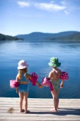 Della Rose Wheatcroft and her friend Sofia Platte stand at the end of a dock holding hands with their bathing suits, sun hats and water wings on. They are on vacation at Priest Lake, Idaho.