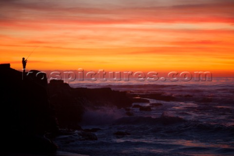 A lone fisherman stands on the rocky shore in La Jolla shore at sunset  San Diego California