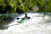 A local kayaker enjoys a kayak surfing session on the 36th Street wave in Boise Idaho. The wave is an infrequent happening, so when the wave is breaking kayakers and whitewater enthusiasts assemble for a day of riding.