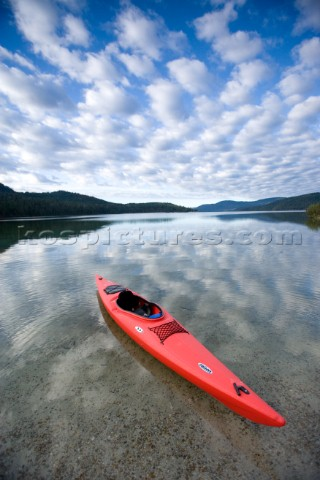 A red sea kayak floats in the shallow reflective waters of Priest Lake in Northern Idaho  The image